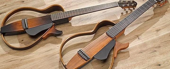 Two Yamaha SLG Silent Guitars on Wooden Floor