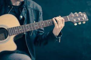 man playing cutaway acoustic electric guitar.com