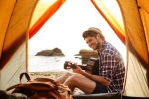 smiling-young-man-sitting-inside-tent-at-the-beach-and-playing-guitar