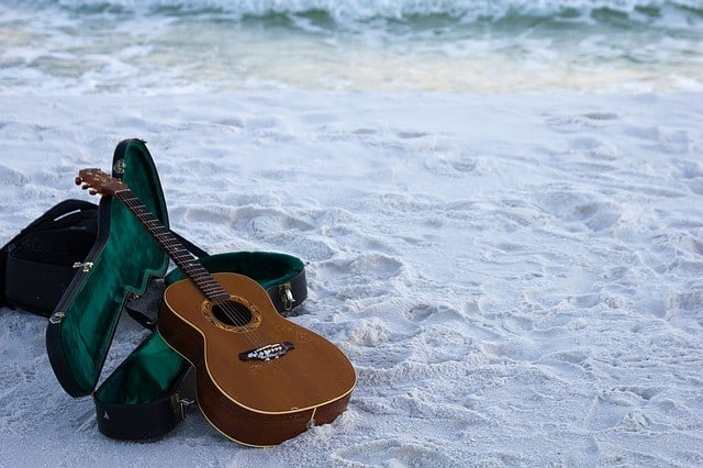Classical guitar lying in the sand