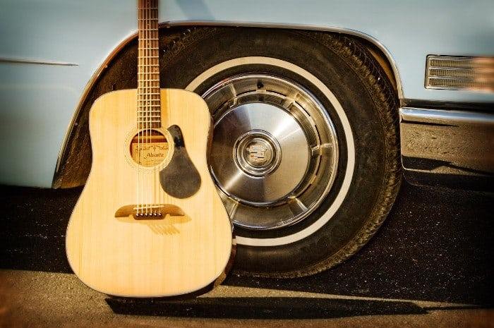 Acoustic Guitar Leaning Against Car Wheel