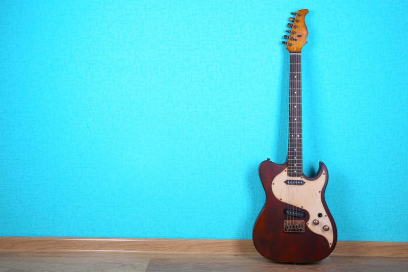 A Cheap Electric Guitar Leaning Against Electric Blue Wall