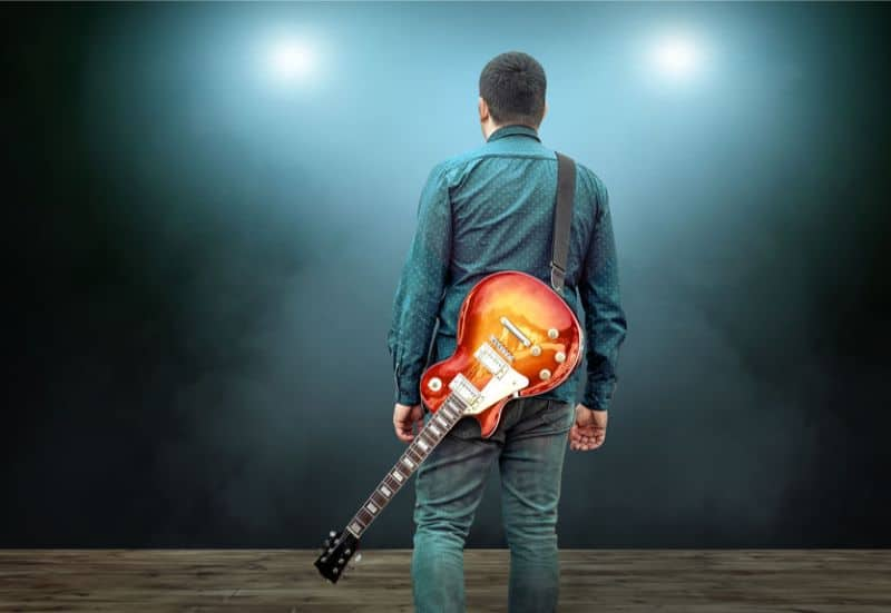 Guitarist Walking With Electric Guitar Hanging Over His Shoulder