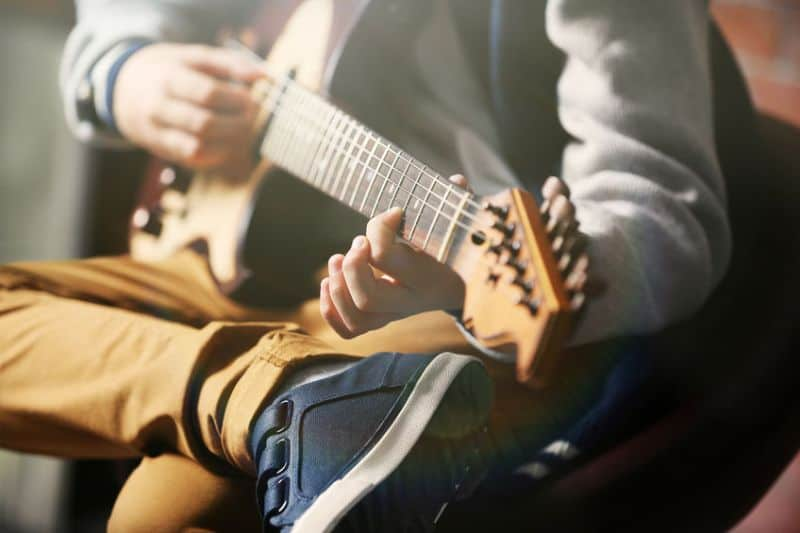 Close Up of Young Boy With Smaller Hands Playing An Electric Guitar