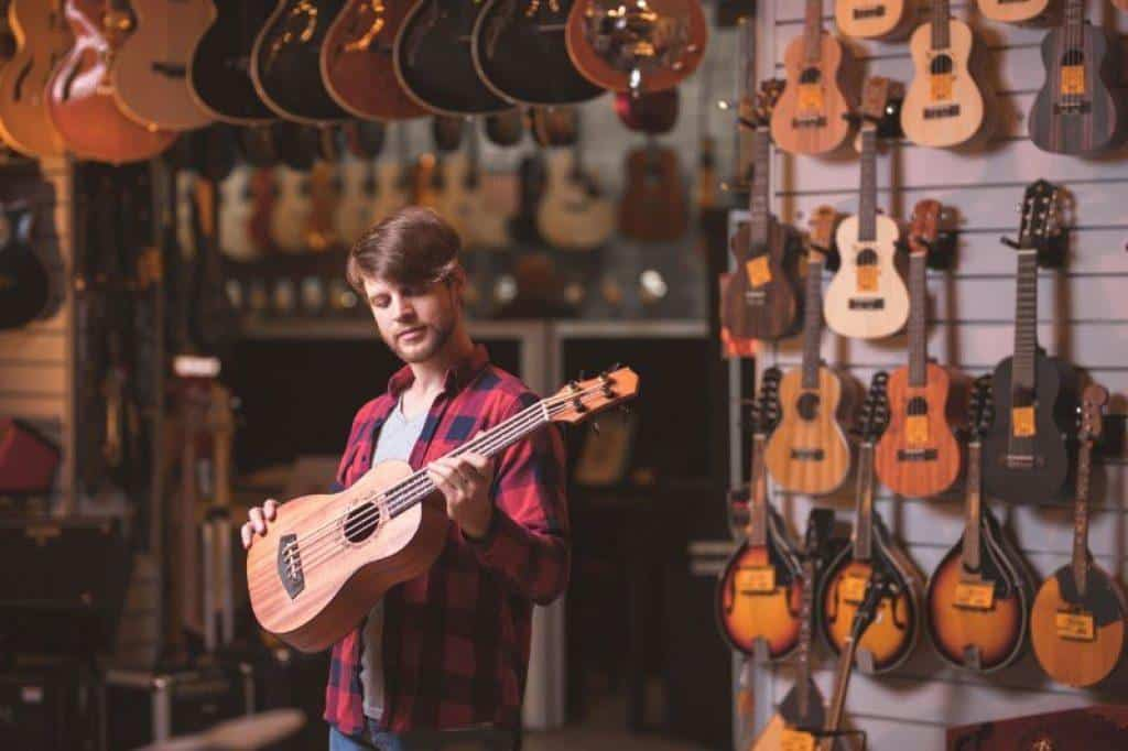 A man holding a Ukulele under $500 and deciding which to buy