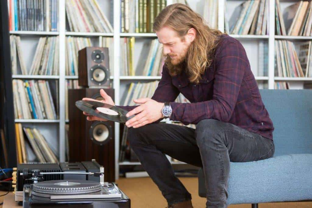 Man holding a record looking at turntable