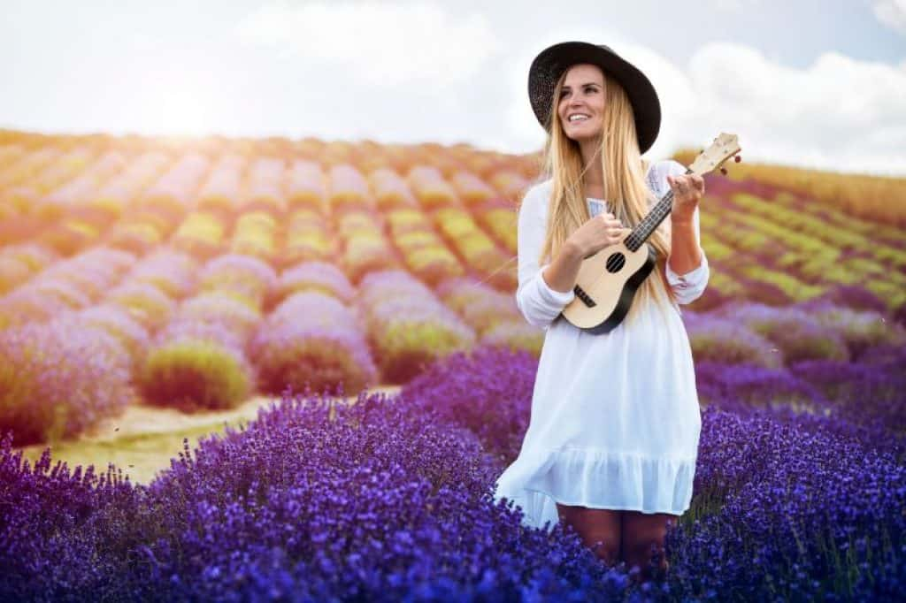 Woman playing an under $300 Ukulele in Field