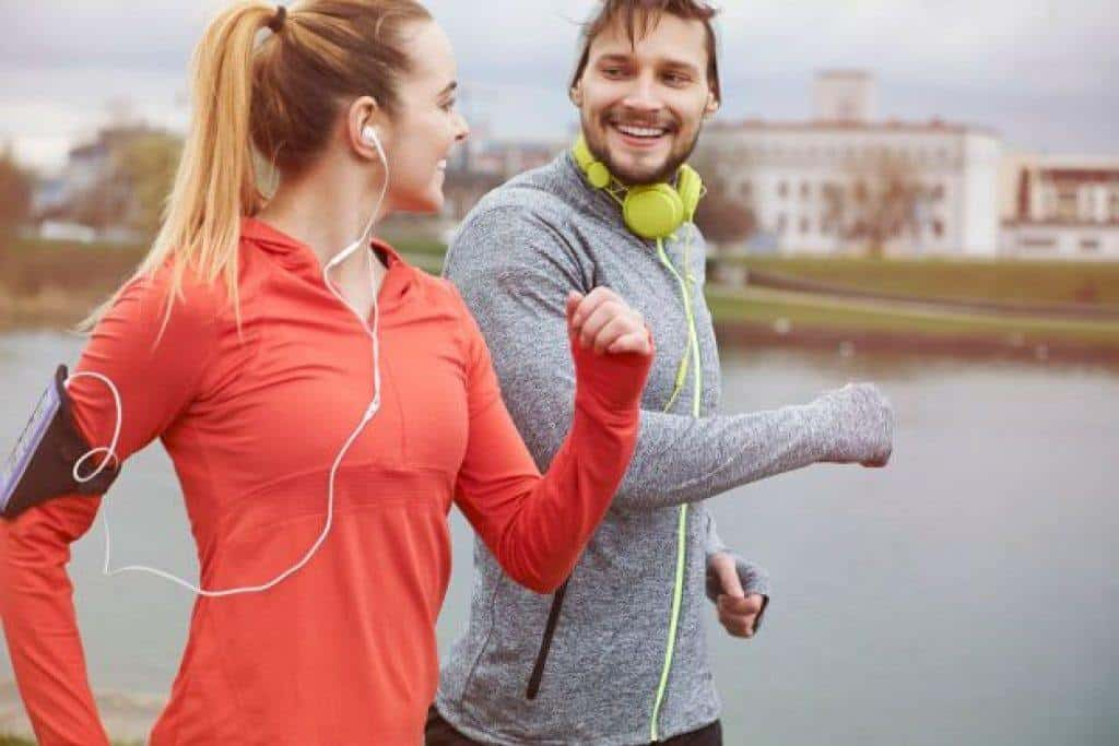 man and woman running with wired headphones