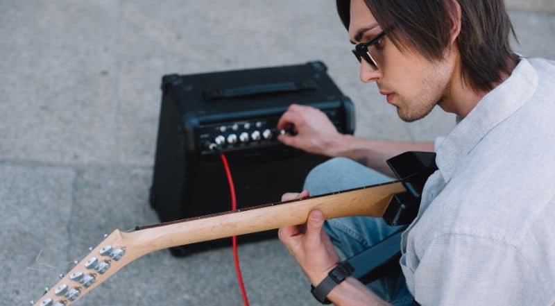 Guitarist Adjusting $500 Amplifier