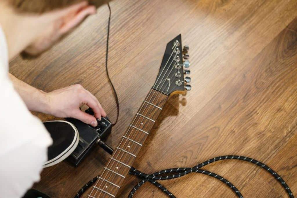 Guitarist adjusting affordable guitar pedal