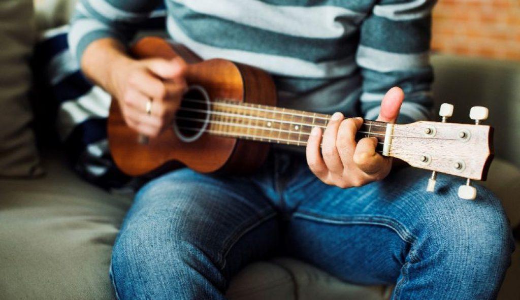Man Playing Inexpensive Ukulele
