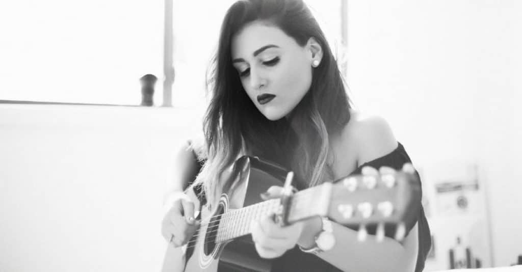 Young Female Guitarist Playing Budget Acoustic Guitar